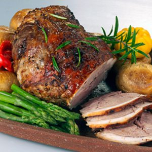 Roasted deboned leg of lamb with roated vegetables and green asparagus spears.